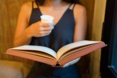 Unga flickan sitter på en soffa och en läsning en bok, medan rymma en pappers- kopp Royaltyfri Bild