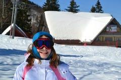 Unga flickan skidar in semesterorten Arkivfoto