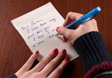 Unga flickan skrivar brevet till Santa Claus på den träskrivbordet och tröjan royaltyfri fotografi
