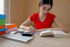 Unga flickan skriver i anteckningsbok mellan böcker Flicka som arbetar på hans läxa ung attraktiv student Girl som studerar kurse Arkivfoto