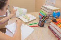 Unga flickan skriver i anteckningsbok mellan böcker Utbildning och skolabegrepp Arkivbild