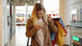 Unga flickan skriver något i hennes telefon som går runt om gallerian med shoppingpåsar stock video