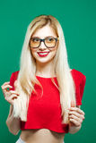 Unga flickan som bär den kort röda överkanten och glasögon, poserar på grön bakgrund Stående av den sinnliga nätta blondinen in Royaltyfri Bild