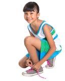Unga flickan som binder skon, snör åt Arkivbilder