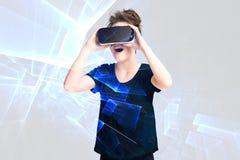 Unga flickan som får erfarenhet genom att använda VR-hörlurar med mikrofonexponeringsglas, är ökat verklighetglasögon och att var Arkivbilder