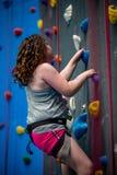 Unga flickan som klättrar upp på övningsväggen in vaggar inomhus, idrottshall arkivbilder