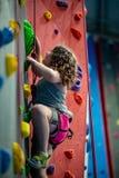 Unga flickan som klättrar upp på övningsväggen in vaggar inomhus, idrottshall arkivfoto