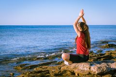 Unga flickan som mediterar på kusten i yoga, poserar Arkivfoton