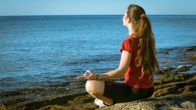Unga flickan som mediterar på kusten i yoga, poserar lager videofilmer