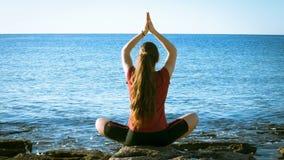 Unga flickan som mediterar på kusten i yoga, poserar arkivfilmer