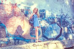 Unga flickan som poserar mot en vägg med grafitti, solen, jeans står på de målade väggarna Arkivbilder