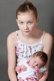 Unga flickan som rymmer ett nyfött, behandla som ett barn arkivbild