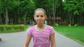 Unga flickan som skateboarding på vägen parkerar in stock video