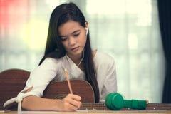 Unga flickan som spelar gitarren och, komponerar musik Royaltyfri Foto