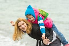 Unga flickan som spelar med henne, behandla som ett barn på naturen nära vattnet i kallt väder Arkivbilder