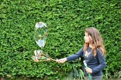 Unga flickan spelar med såpbubblor i en trädgård Arkivbilder