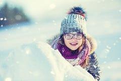 Unga flickan spelar med snö Lycklig flicka Blowin för skönhetvinter royaltyfria foton