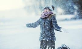 Unga flickan spelar med snö Parkerar den lyckliga flickan för skönhetvintern som blåser insnöad frostig vinter, eller utomhus arkivbilder