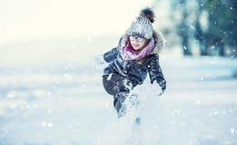 Unga flickan spelar med snö Parkerar den lyckliga flickan för skönhetvintern som blåser insnöad frostig vinter, eller utomhus royaltyfri foto
