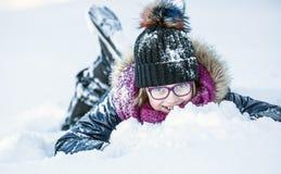 Unga flickan spelar med snö Parkerar den lyckliga flickan för skönhetvintern som blåser insnöad frostig vinter, eller utomhus royaltyfri fotografi