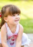 Unga flickan spelar utomhus Arkivfoto