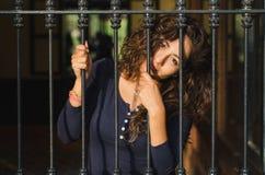 Unga flickan stängde sig bak stänger, nätverk, som i fängelse royaltyfri fotografi