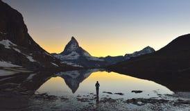 Unga flickan står framme av sjön var Matterhornen 4478m och Dente Blanche 4357m reflekterade i Riffelseen Arkivbild