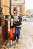 Unga flickan står nära en hög tabell för gata med uppvärmning royaltyfria bilder