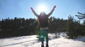 Unga flickan står på bakgrund av en vinterskog och lyfter henne armar Kvinna som tycker om vinterlandskapet Frihet lager videofilmer
