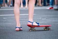 Unga flickan startar att köra på skateboarden i skuggan utomhus arkivfoton
