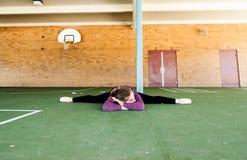 Unga flickan sträcker henne ben fotografering för bildbyråer