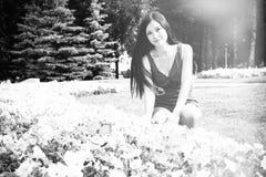 Unga flickan student, sitter nära blommorna i parkera Arkivfoton