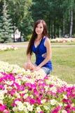 Unga flickan student, sitter nära blommorna i parkera Royaltyfri Foto