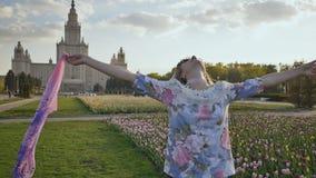 Unga flickan svävar och flyger godlynt med en näsduk i henne händer Varm sommarafton i parkera arkivfilmer