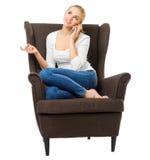Unga flickan talar vid mobiltelefonen i stol royaltyfri foto