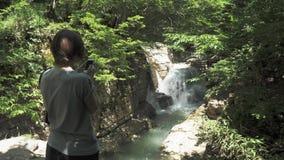 Unga flickan tar fotoet av den lilla vattenfallet, Georgia stock video
