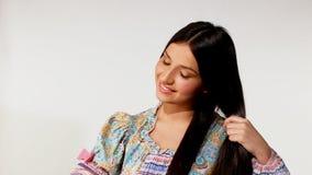 Unga flickan tar omsorg av långt hår - etnisk dräkt arkivfilmer
