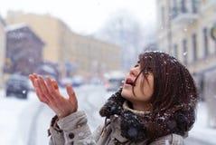 Unga flickan tycker om snön på gatan Royaltyfria Bilder