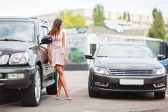 Unga flickan väljer en använd bil i en parkeringsplats ny köpande bil Royaltyfri Bild