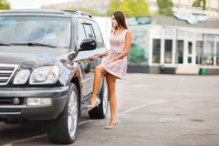 Unga flickan väljer en använd bil i en parkeringsplats ny köpande bil Royaltyfri Foto