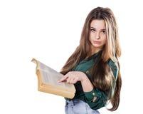 Unga flickan visar ett finger i boken på isolaten Läser Arkivbild