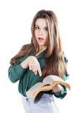 Unga flickan visar ett finger i boken på isolaten Läser Fotografering för Bildbyråer