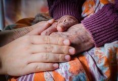 Unga flickans hand trycker på och rymmer en hand för gammal kvinna Royaltyfri Foto