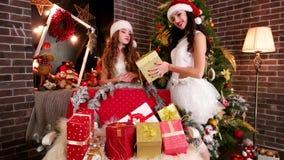 Unga flickor förbereder gåvor för nytt år, den Santa Claus hjälpredan, som packar gåvor, glade skönheter förbereder sig för jul,  stock video