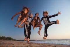Unga flickor i allhelgonaaftondräkter hoppar högt med gyckel Royaltyfri Bild