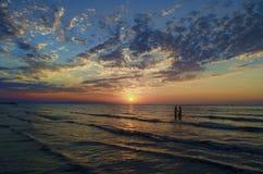 Unga flickor i varmt vatten på solnedgången Ursnygga färger i himlen och havet Folk som står och håller ögonen på till solnedgång Royaltyfria Bilder