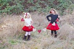Unga flickor med rad av hjärtor royaltyfria foton
