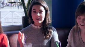 Unga flickor meddelar och dricker den läckra drycken i extra- tid på helg stock video