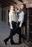 Unga flickor mot en tegelstenvägg Arkivfoton