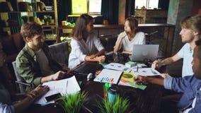 Unga flickor och grabbkollegor har diskussion under lagmöte i skrivbord för arounf för sammanträde för vindstilkontor och arkivfilmer